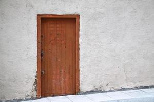 Puerta de madera marrón sobre una pared blanca foto