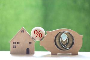 Pila de monedas en una alcancía de madera, una casa modelo y un símbolo de porcentaje sobre un fondo verde natural foto