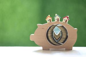 Stack of coins in a wooden piggy bank with model houses on a natural green background photo
