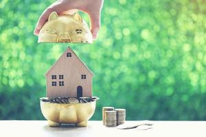 Stack of coins in a golden piggy bank with a model house on a natural green background photo