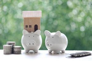 Pila de monedas junto a una alcancía con una casa modelo sobre un fondo verde natural