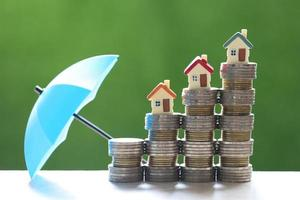Model houses on stacks of coins with an umbrella on a nature green background, finance insurance and safe investment concept