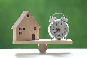 Retro alarm clock and model house on a wood scale on a natural green background, business investment and real estate concept photo