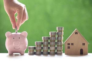Casa modelo con montones de monedas junto a una mano poniendo dinero en una alcancía sobre un fondo verde natural, ahorrando dinero para la preparación del futuro y el concepto de inversión