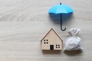 Casa modelo casa modelo y un paraguas sobre un fondo de madera, seguro financiero y concepto de inversión segura foto