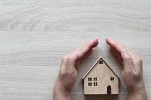 Mano protegiendo una casa modelo sobre un fondo de madera, seguro financiero y concepto de inversión segura foto