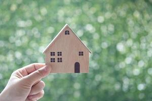 Woman's hand holding a model house on a natural green background, business investment and real estate concept photo