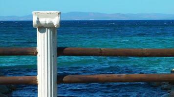 antigua columna de mármol y el mar. video