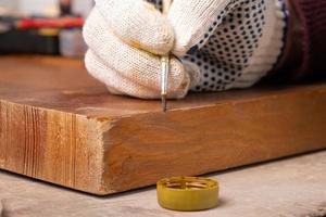 una mano eliminando los defectos de las astillas con un pincel, restauración de puertas de madera foto