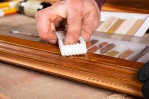 una mano restaurando una puerta de madera eliminando los defectos de viruta foto