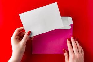 Un sobre de felicitación en manos de una mujer joven sobre un fondo rojo. foto