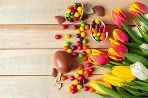 Beautiful red and yellow tulips for easter holiday. Chocolate eggs and candies on a wooden background. photo