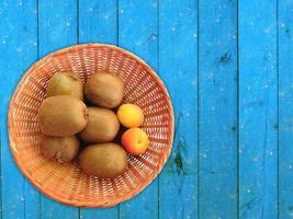 Kiwis y albaricoques en una cesta de mimbre sobre un fondo de mesa de madera foto
