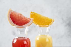 Two glasses of grapefruit and orange juice on A stone background photo