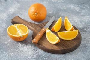 frutas naranjas enteras y en rodajas con un cuchillo colocado sobre una tabla redonda de madera