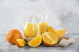 Jars of fresh orange juice and orange fruits on a stone background photo