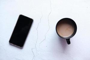 composición plana de teléfono inteligente y café en la mesa foto