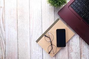 teléfono inteligente, computadora portátil y bloc de notas en la mesa con espacio de copia foto