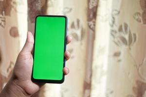 Hombre sujetando un teléfono inteligente con pantalla verde foto
