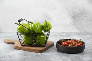 Red cherry tomatoes with green bell peppers placed on a stone table