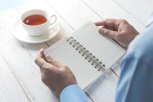 Man's hand turning the page of a notepad photo