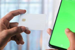 pantalla verde en un teléfono con una persona que tiene una tarjeta de crédito