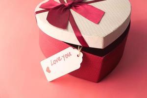 Caja de regalo con forma de corazón sobre fondo rosa foto