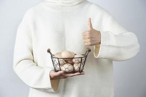 Manos femeninas con una canasta metálica de huevos de gallina crudos mostrando un pulgar hacia arriba foto