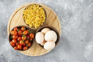 Raw chicken eggs with uncooked shell-shaped pasta and red cherry tomatoes
