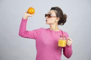 mujer joven en un suéter rosa mostrando una naranja fresca y jugo foto