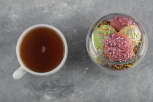 A glass jar full of small colorful doughnuts with a cup of hot tea photo