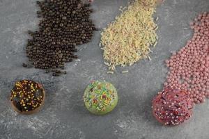 Set of sweet doughnuts with sprinkles and three jars of sprinkles photo