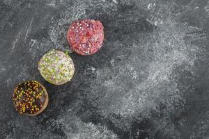 Three colorful sweet doughnuts with sprinkles photo
