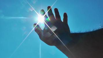 Hand is reaching to the Sun video