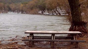 Asiento de madera y lago en invierno.