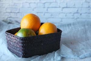 Fruta naranja en un recipiente sobre fondo neutro