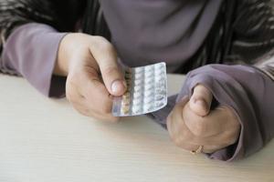 mujer sosteniendo pastillas anticonceptivas foto