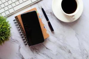 Vista superior del teléfono inteligente y el bloc de notas en la mesa foto