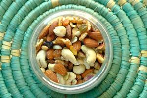 Nueces mixtas en un recipiente sobre mantel azul foto