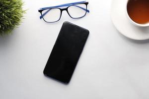 Vista superior del teléfono inteligente, anteojos y té en la mesa foto