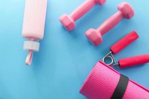 mancuernas de color rosa, zapatos y auriculares sobre fondo azul foto