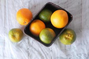 Vista superior de las naranjas en un recipiente sobre fondo neutro