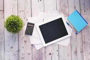 tableta digital con suministros de oficina en la mesa foto