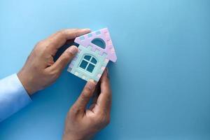 Man holding model house on blue background photo