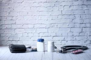 Estetoscopio y pastillas sobre fondo de madera foto