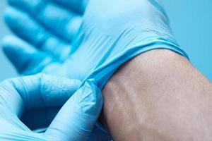 Doctor removing medical gloves, close up photo