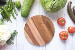 Selección de alimentos saludables con verduras frescas y una tabla de cortar.