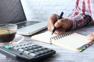 Cerca de la mano del hombre escribiendo en un bloc de notas