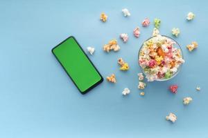 Vista superior del teléfono inteligente y palomitas de maíz sobre fondo azul. foto