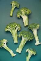 Loose broccoli on dark green background photo